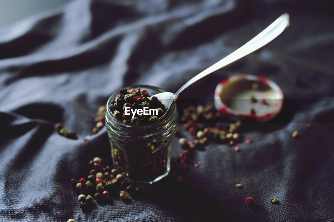 Close-Up Of Black Peppercorns In Jar On Fabric