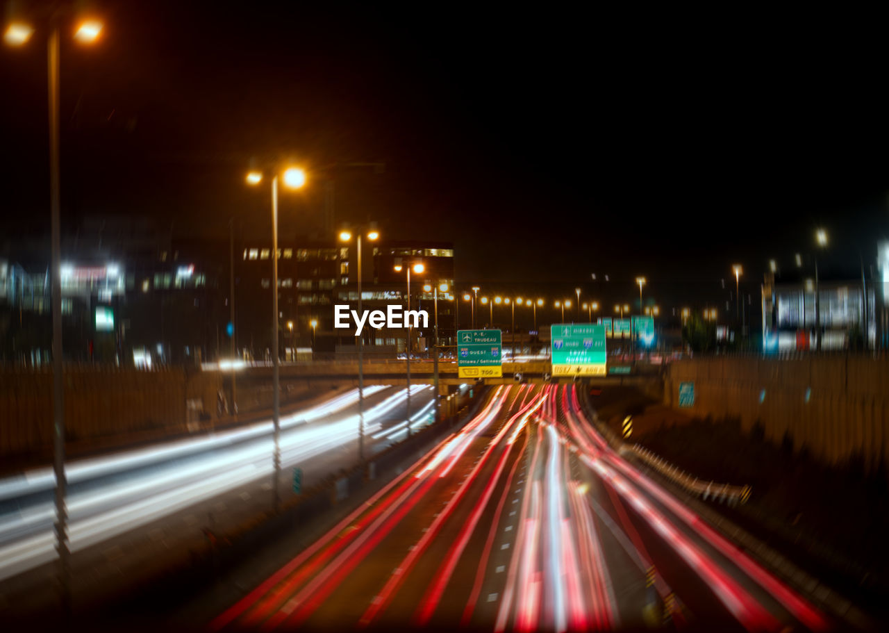 BLURRED MOTION OF LIGHT TRAILS ON HIGHWAY AT NIGHT