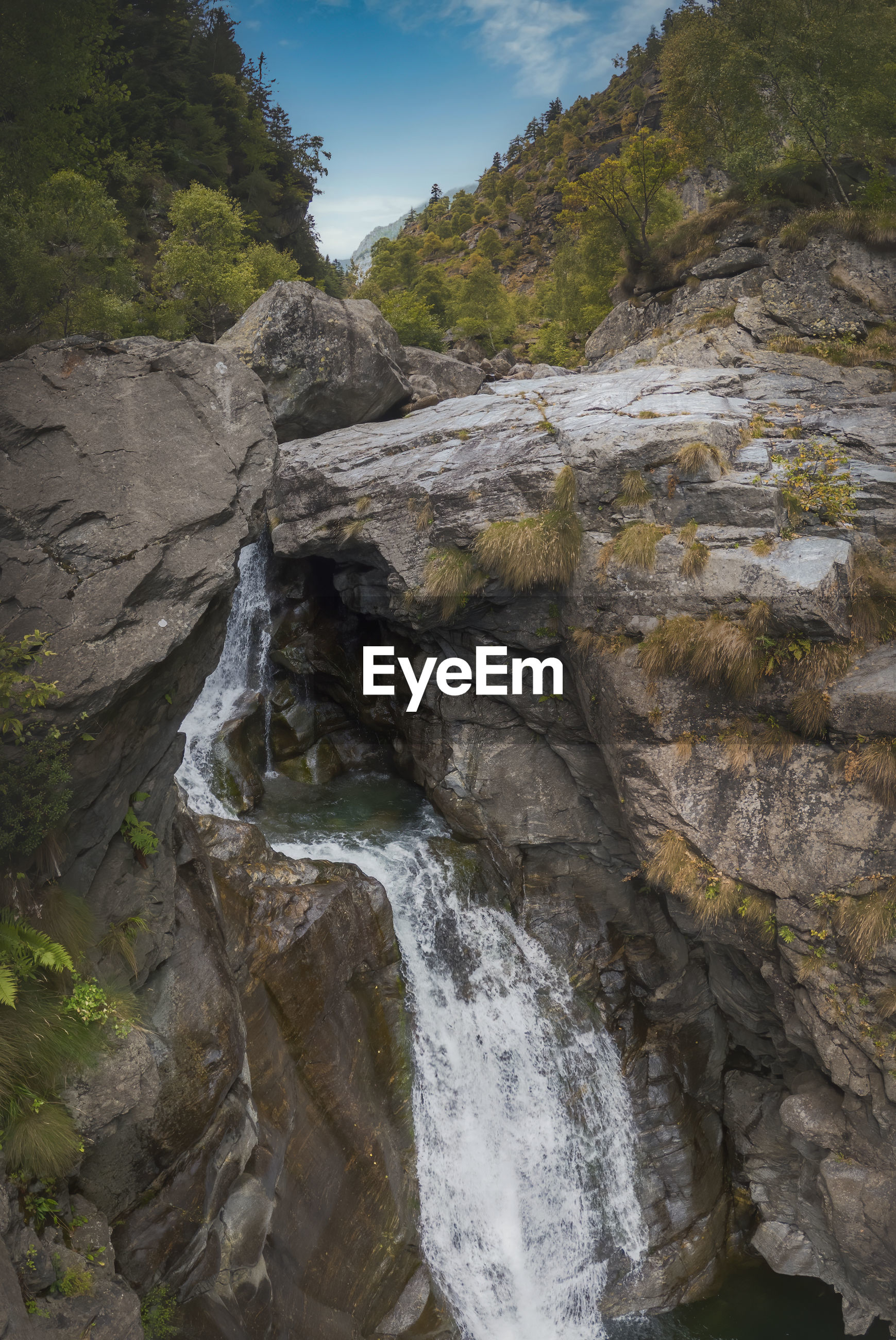 SCENIC VIEW OF WATERFALL ON ROCK FORMATION