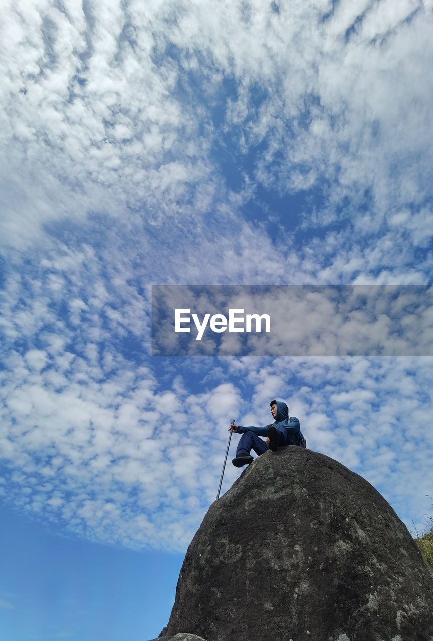 LOW ANGLE VIEW OF WOMAN SITTING ON ROCKS AGAINST SKY