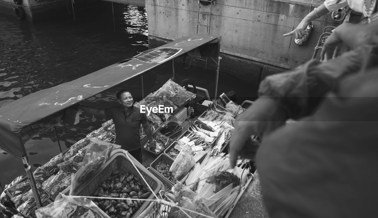 High Angle View Of Market Vendor Selling Seafood On Boat