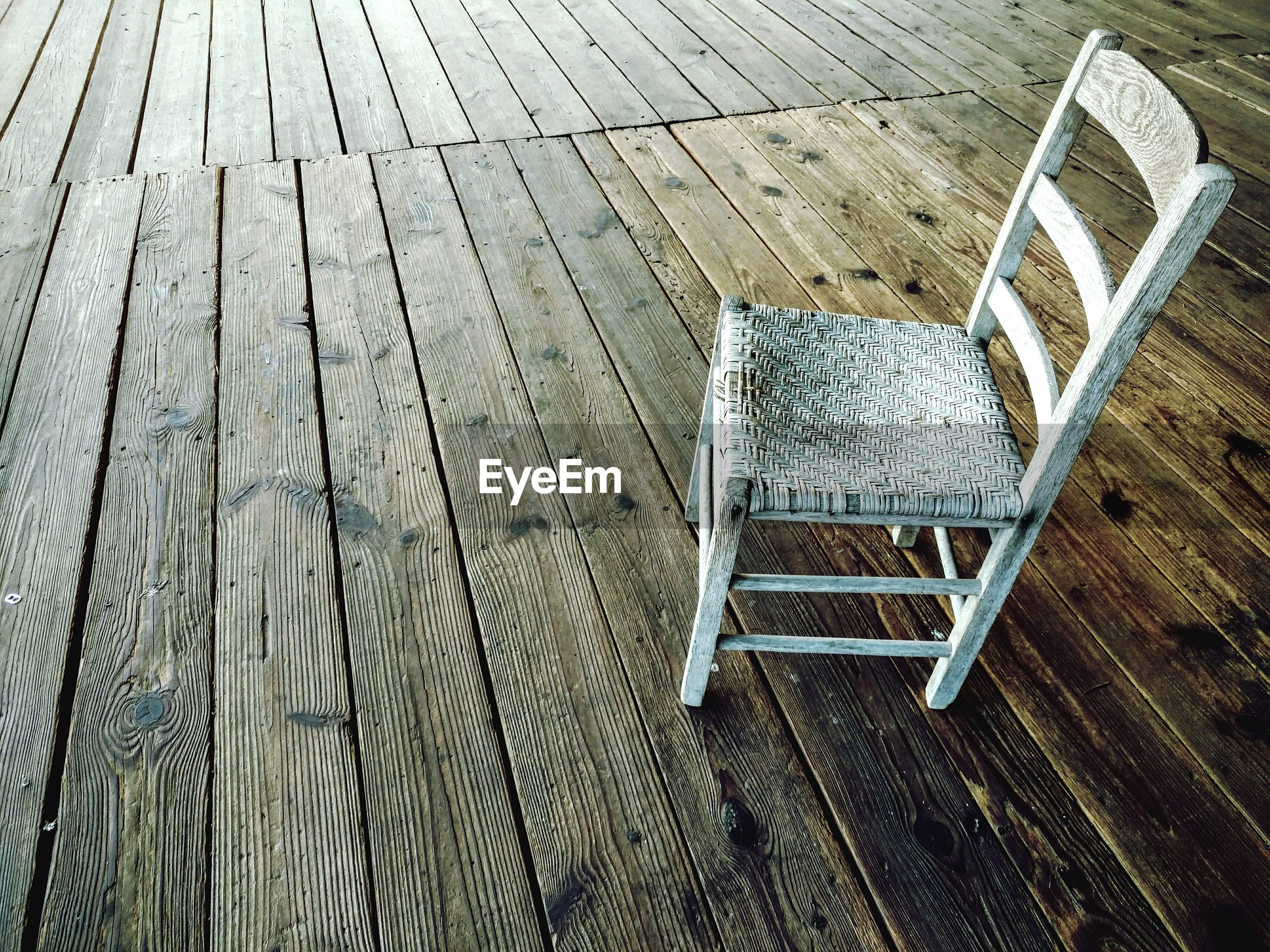 High angle view of white empty chair on boardwalk