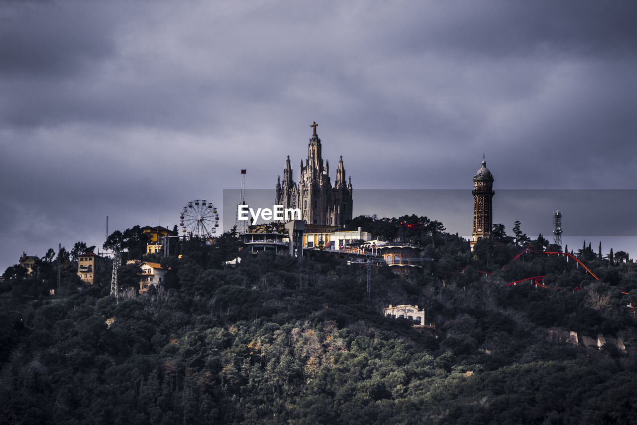 View of amusement park in city on top of a hill against cloudy sky
