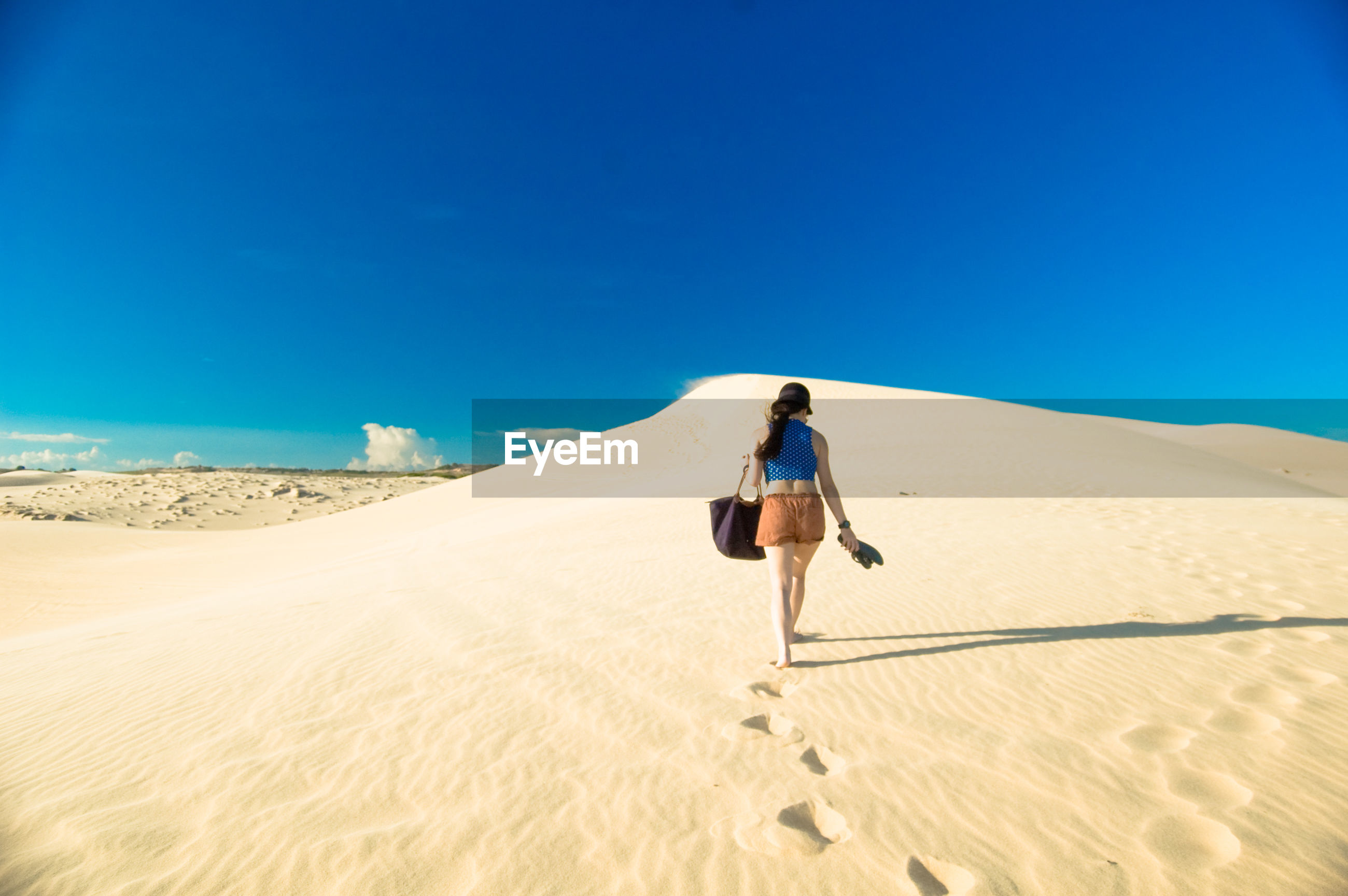 Young woman walking in desert against clear blue sky