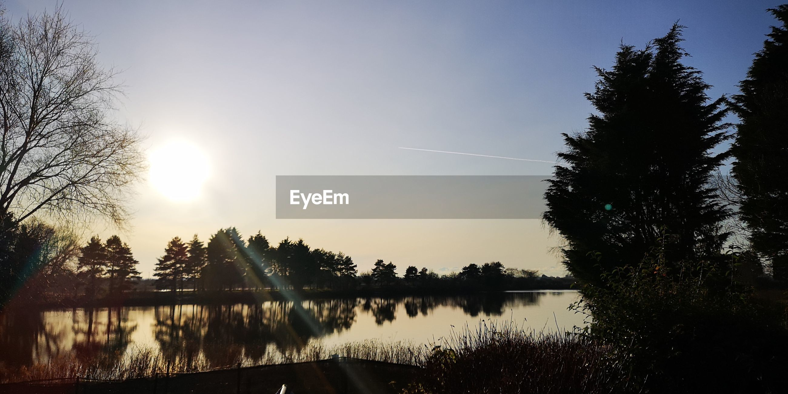 Scenic view of lake against clear sky during sunset
