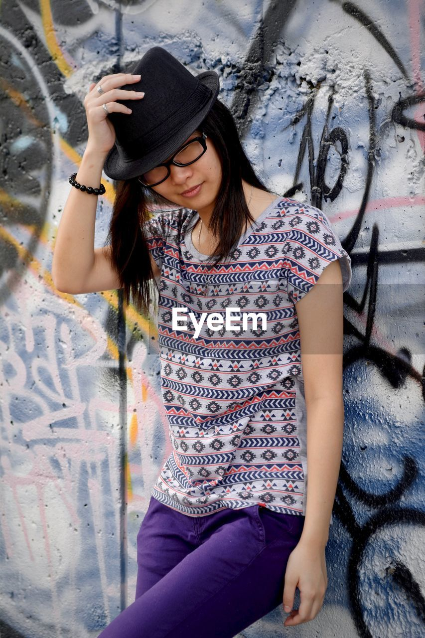 one person, real people, three quarter length, leisure activity, front view, lifestyles, young women, graffiti, clothing, hat, casual clothing, young adult, wall - building feature, women, holding, fashion, sitting, hair, hairstyle, teenager