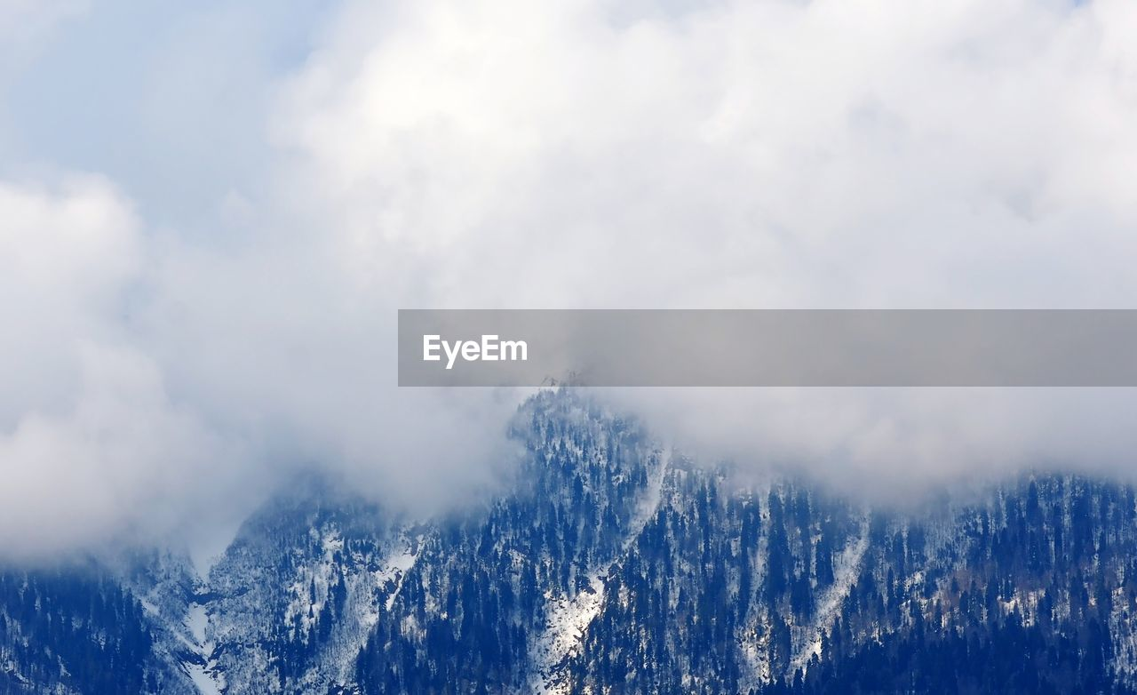 cloud - sky, beauty in nature, sky, mountain, scenics - nature, nature, day, non-urban scene, tranquil scene, no people, tranquility, mountain range, winter, outdoors, environment, snow, cold temperature, smoke - physical structure, white color, snowcapped mountain, mountain peak, pollution