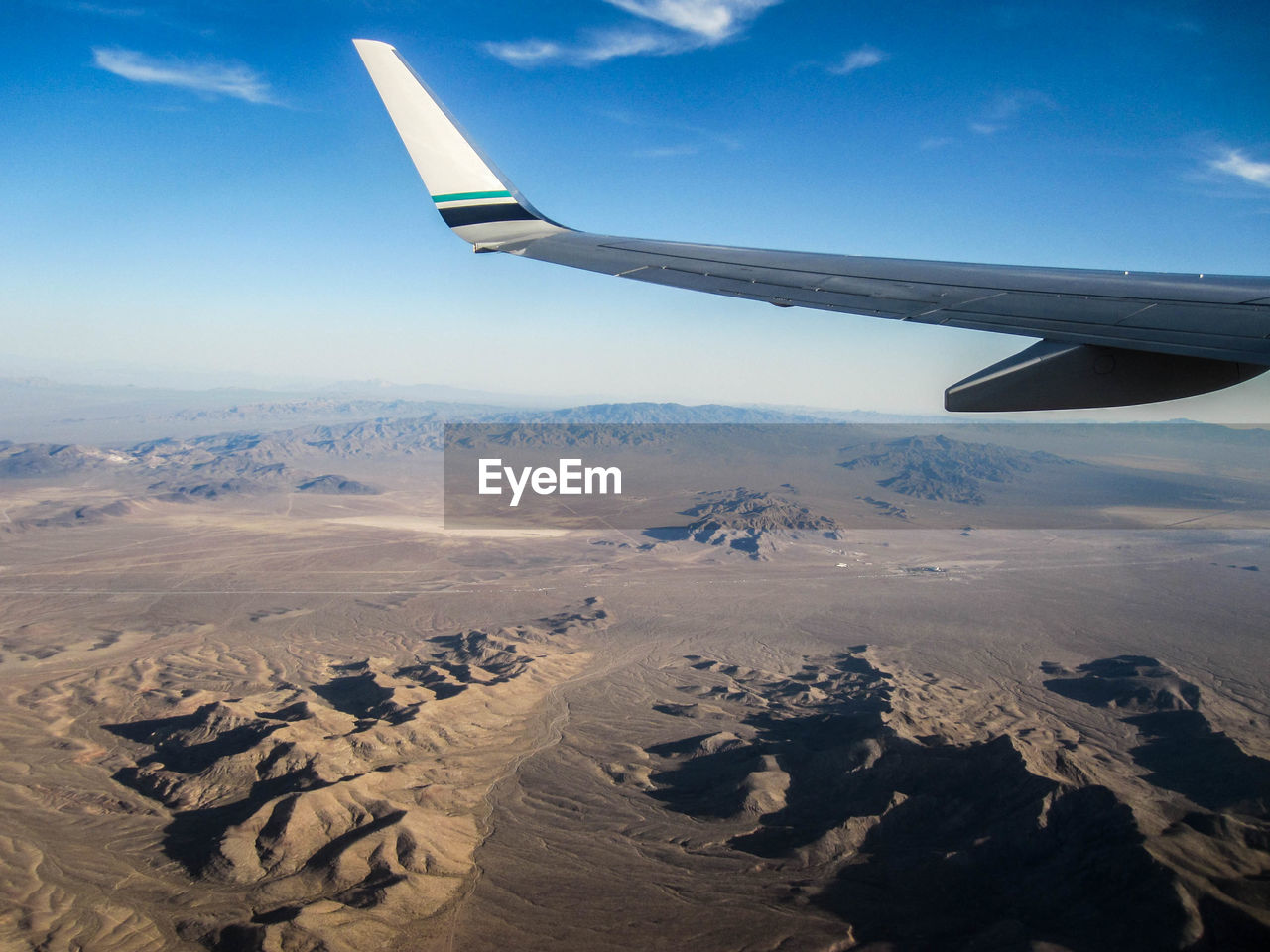 Cropped Image Of Airplane Wing Flying Over Mountains