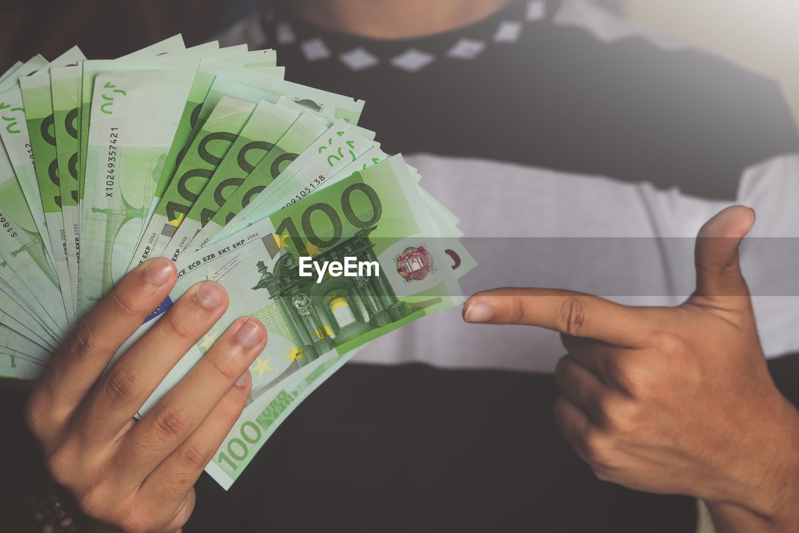 Midsection of man pointing at fanned out green paper currencies