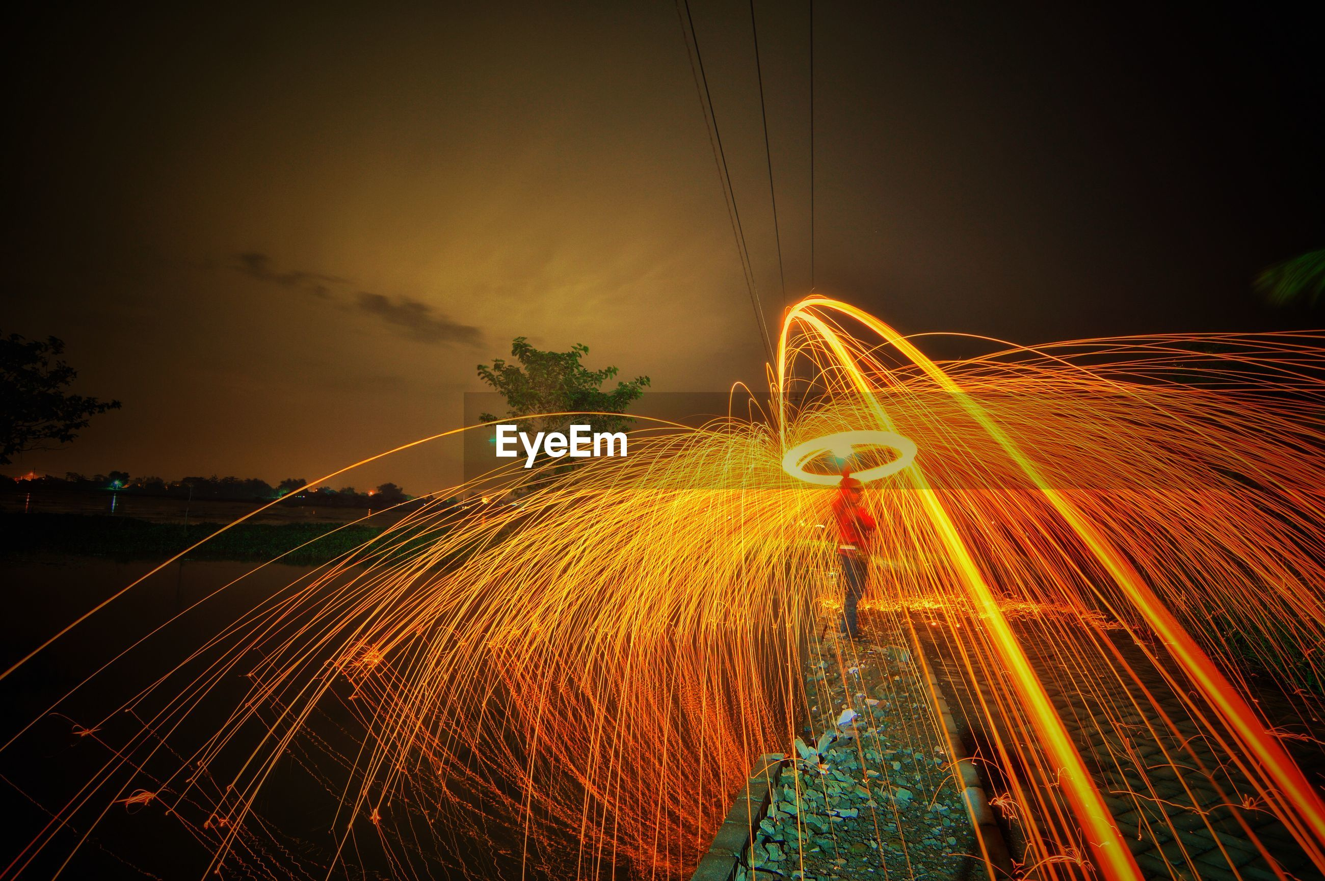 Man spinning wire wool at night