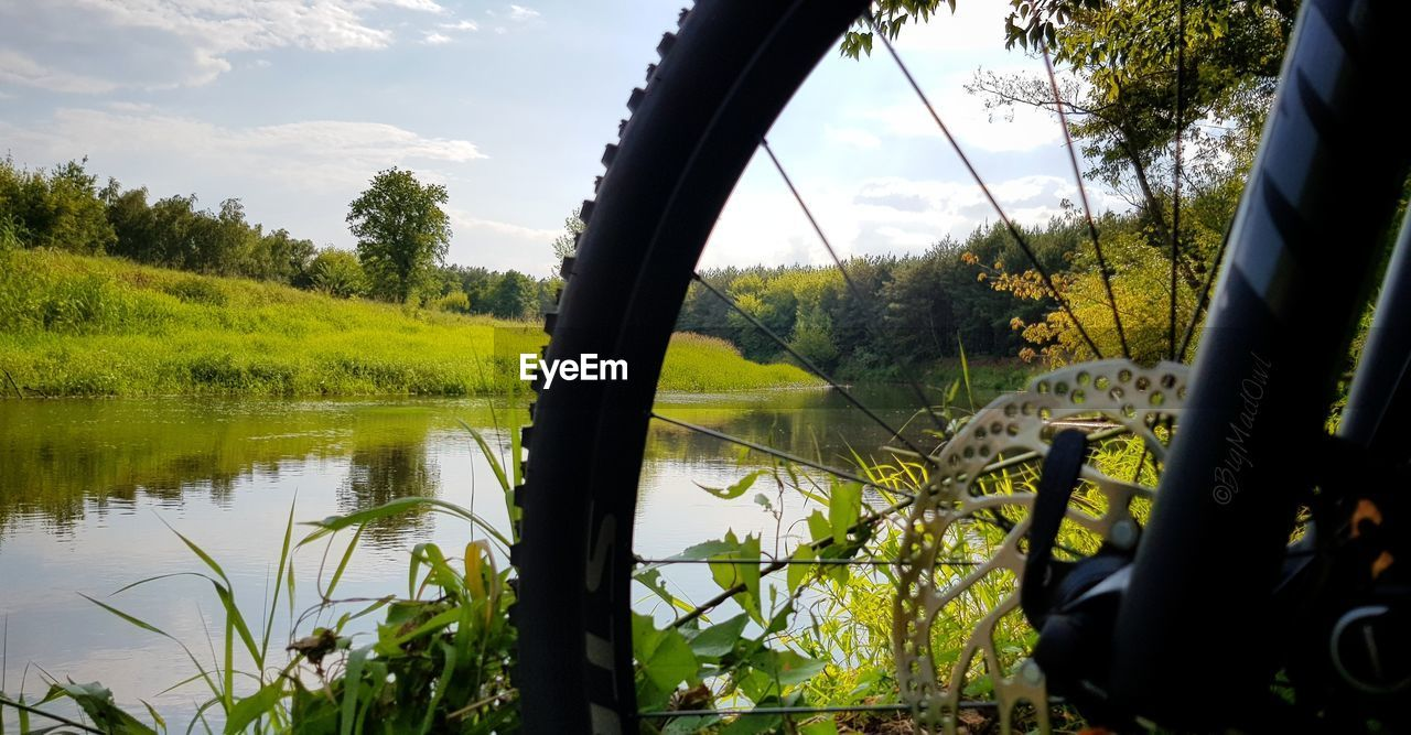 Close-up of bicycle parked by lake