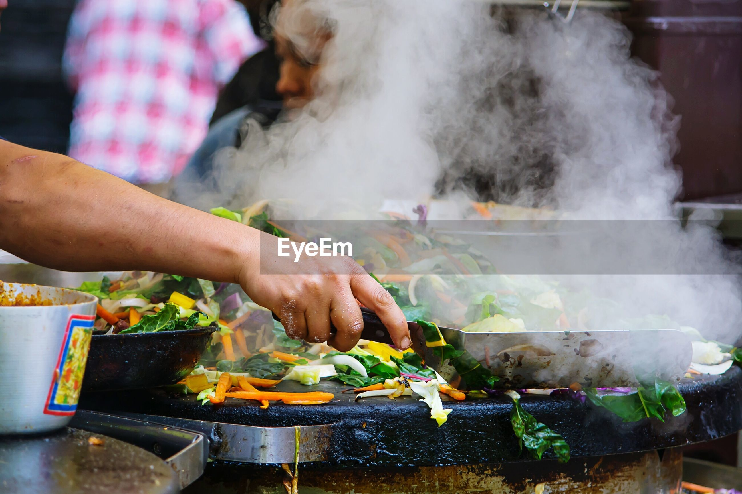Cropped image of person preparing vegetables at market stall