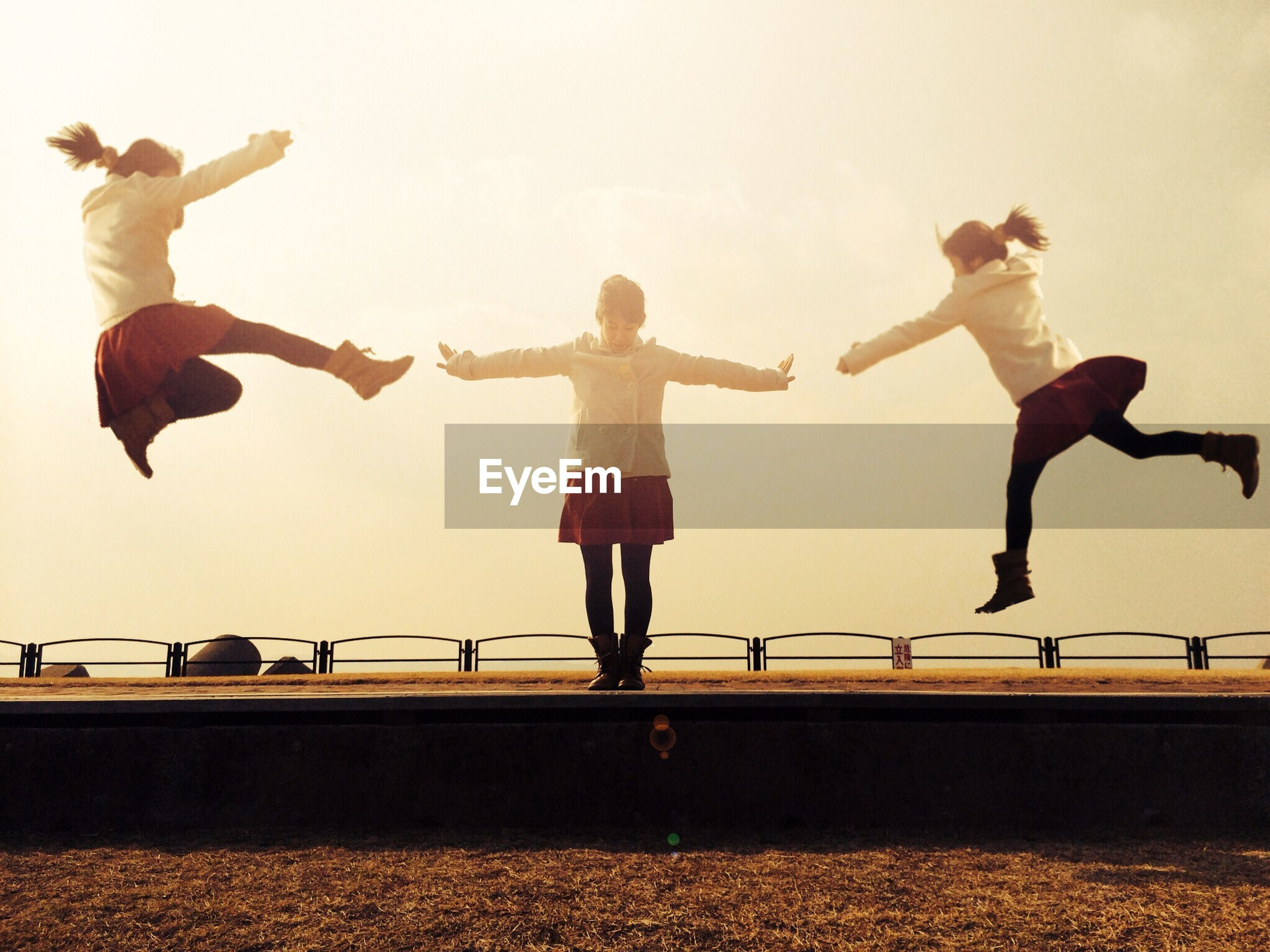 full length, lifestyles, leisure activity, standing, jumping, clear sky, mid-air, fun, men, casual clothing, walking, enjoyment, arms outstretched, person, togetherness, childhood, copy space