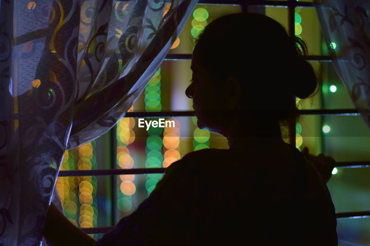 Rear view of woman looking through window at home during night