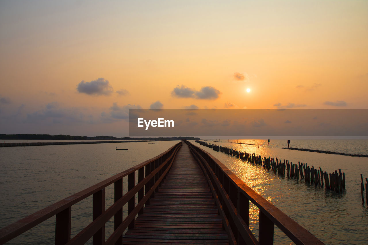 sky, water, sunset, scenics - nature, tranquil scene, tranquility, beauty in nature, sea, railing, the way forward, horizon over water, wood - material, direction, nature, horizon, pier, orange color, idyllic, diminishing perspective, no people, outdoors, sun, long