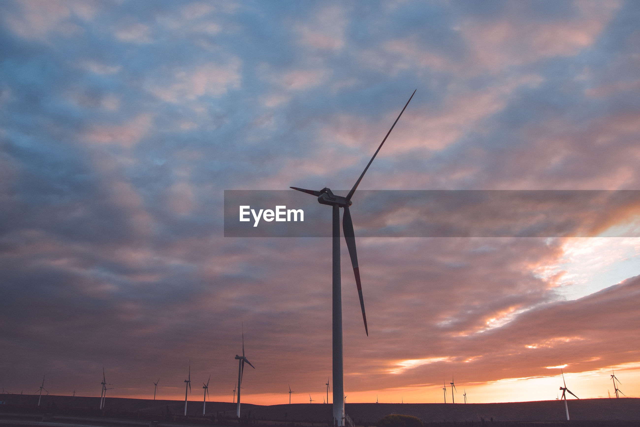 Low angle view of silhouette wind turbine against sky during sunset