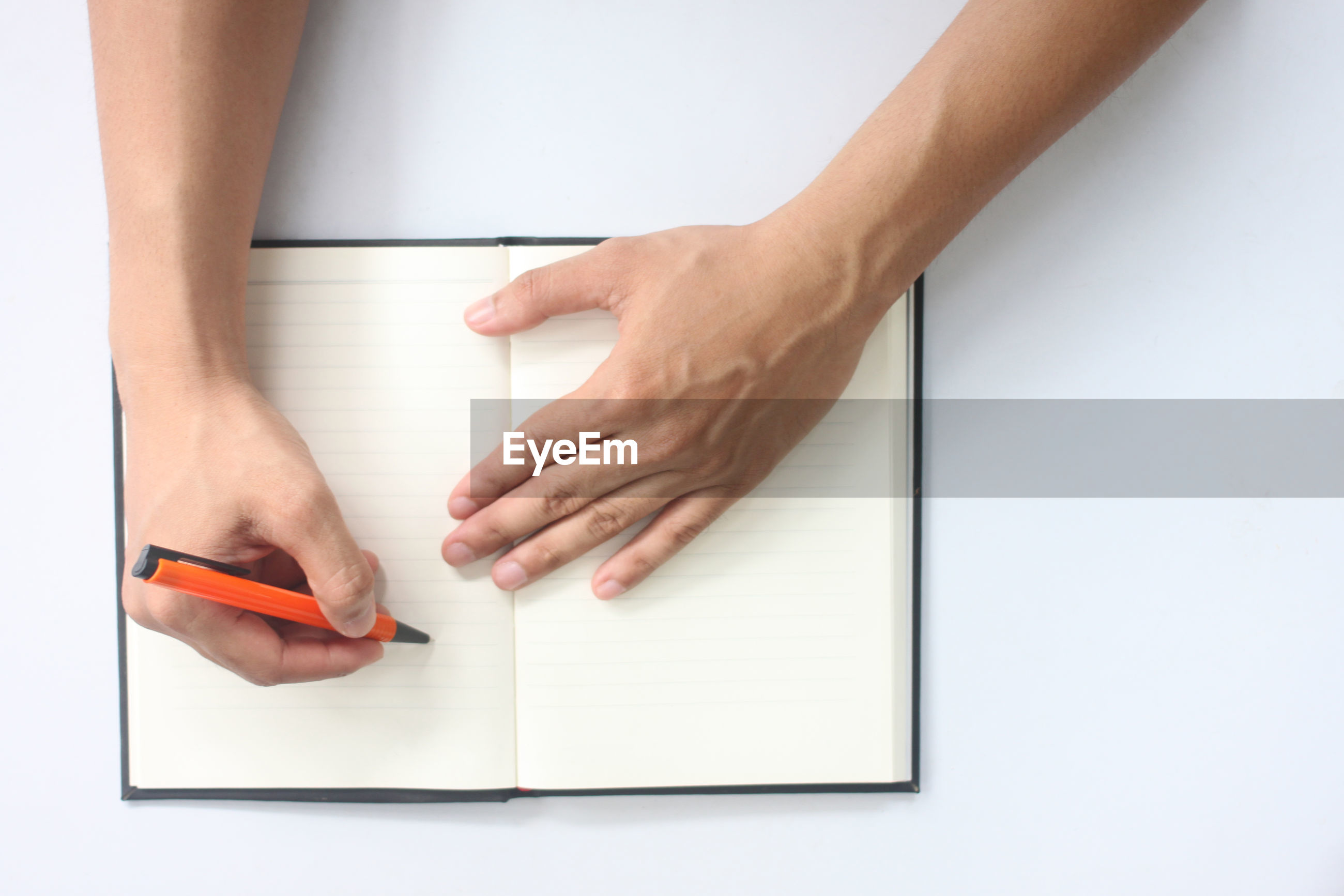 Cropped hands of person writing in book against white background