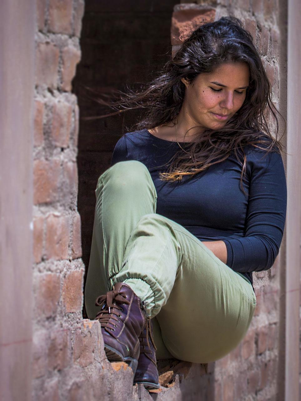 Young Woman Sitting On Broken Brick Wall