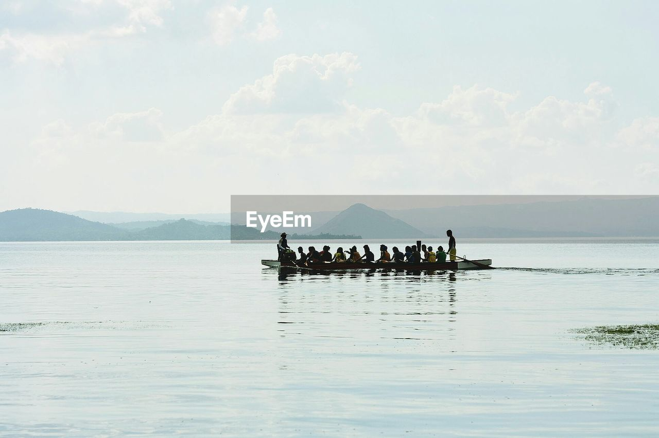People moving in row boat at lake against cloudy sky