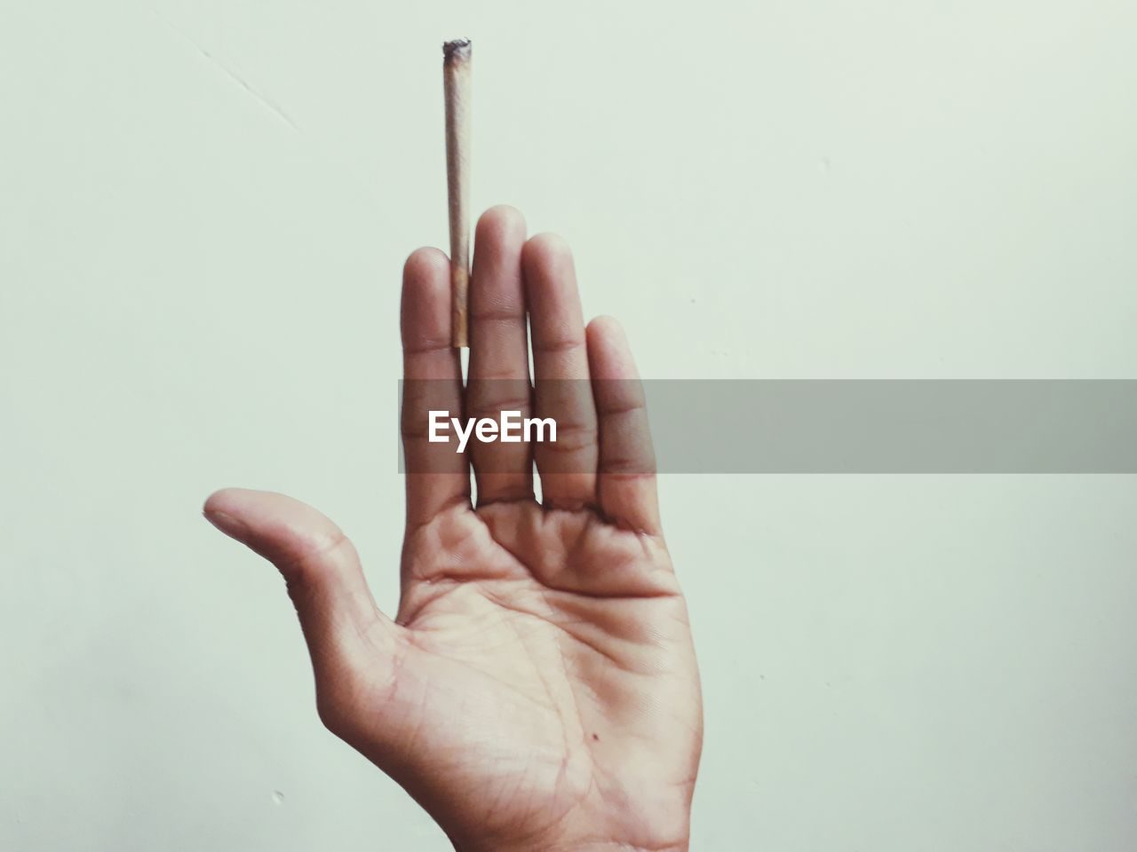 Close-Up Of Hand Holding Marijuana Joint Against White Background
