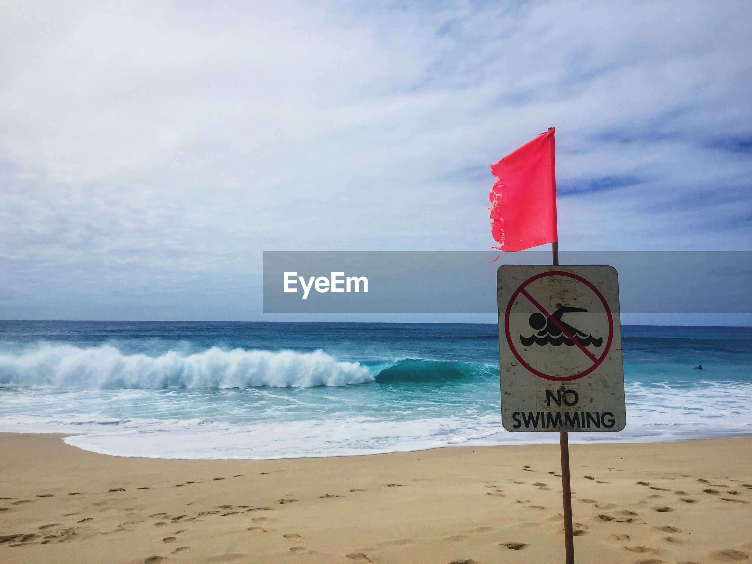 CLOSE-UP OF SIGN ON BEACH AGAINST SKY