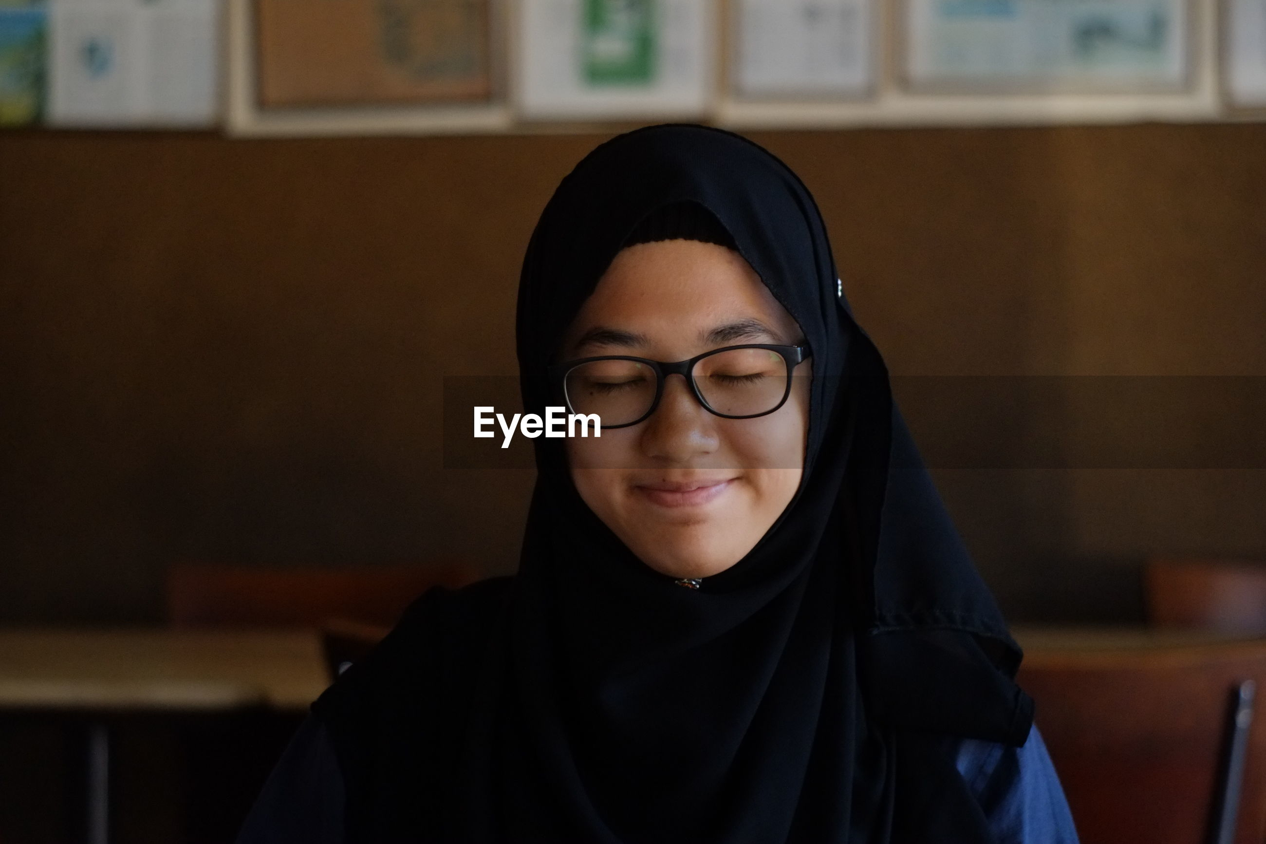 Close-up of happy girl wearing hijab and eyeglasses with closed eyes at restaurant