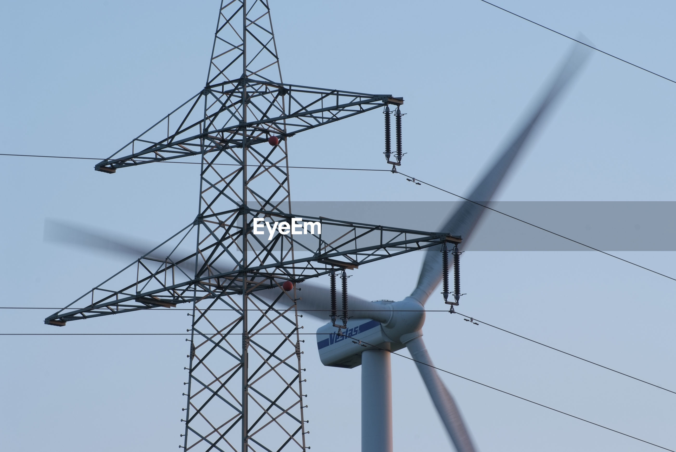low angle view, clear sky, day, outdoors, cable, no people, electricity, sky, technology, electricity pylon, architecture
