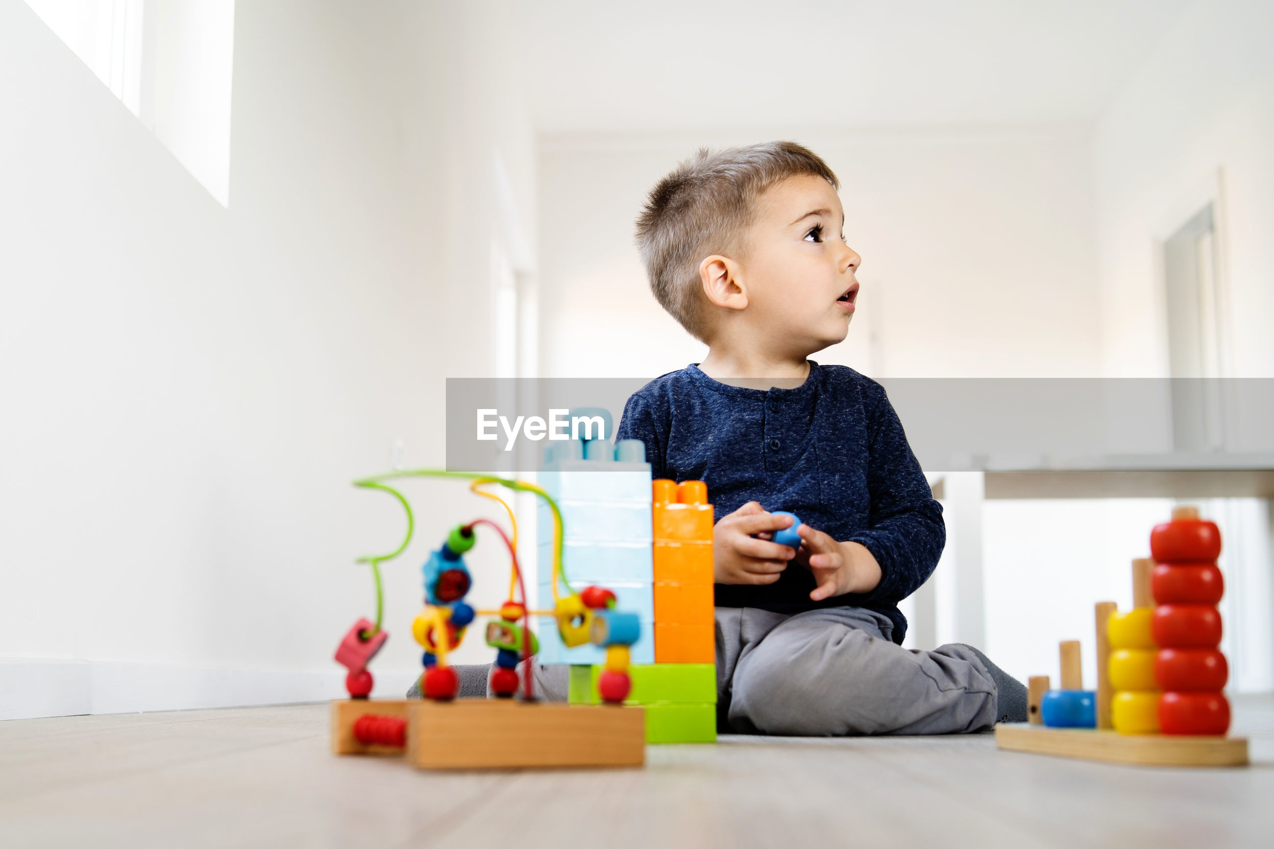 Cute boy looking away while playing on floor at home