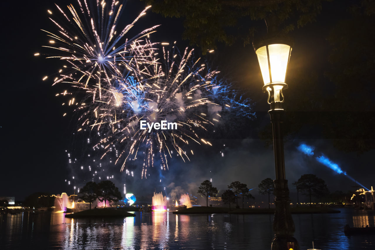 night, illuminated, firework display, celebration, glowing, firework - man made object, lighting equipment, long exposure, exploding, arts culture and entertainment, outdoors, low angle view, street light, firework, event, sky, no people, waterfront, multi colored, water, architecture, city