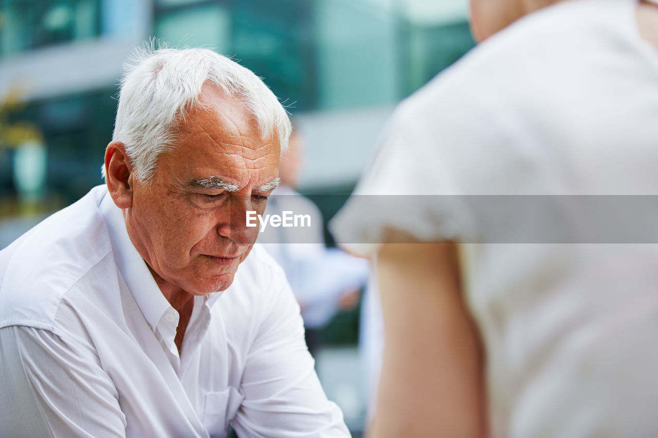 Senior Businessman With Woman Sitting Outdoors