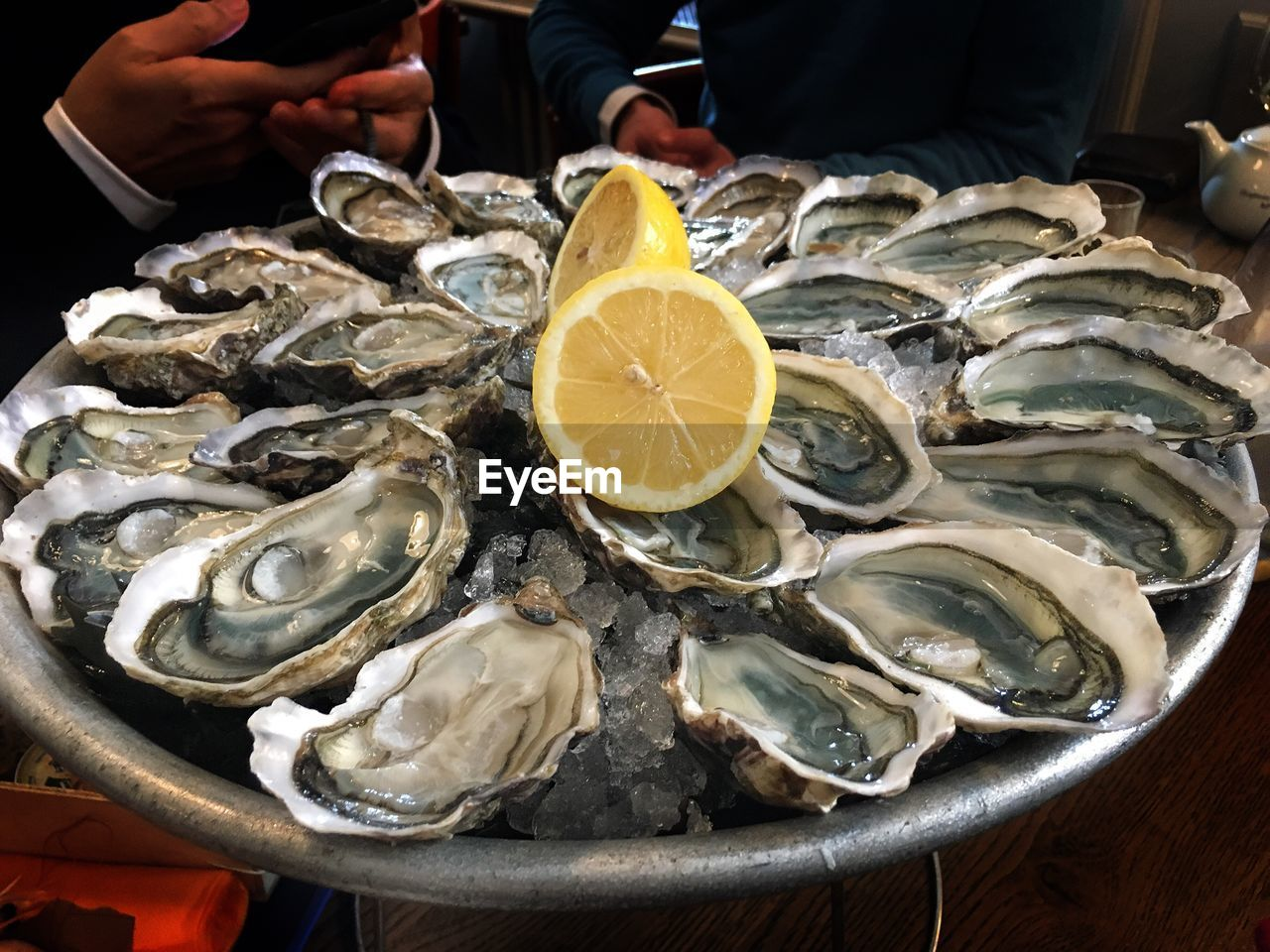 seafood, food and drink, human hand, food, real people, one person, lemon, oyster, freshness, human body part, healthy eating, men, holding, table, indoors, day, close-up, ready-to-eat, people