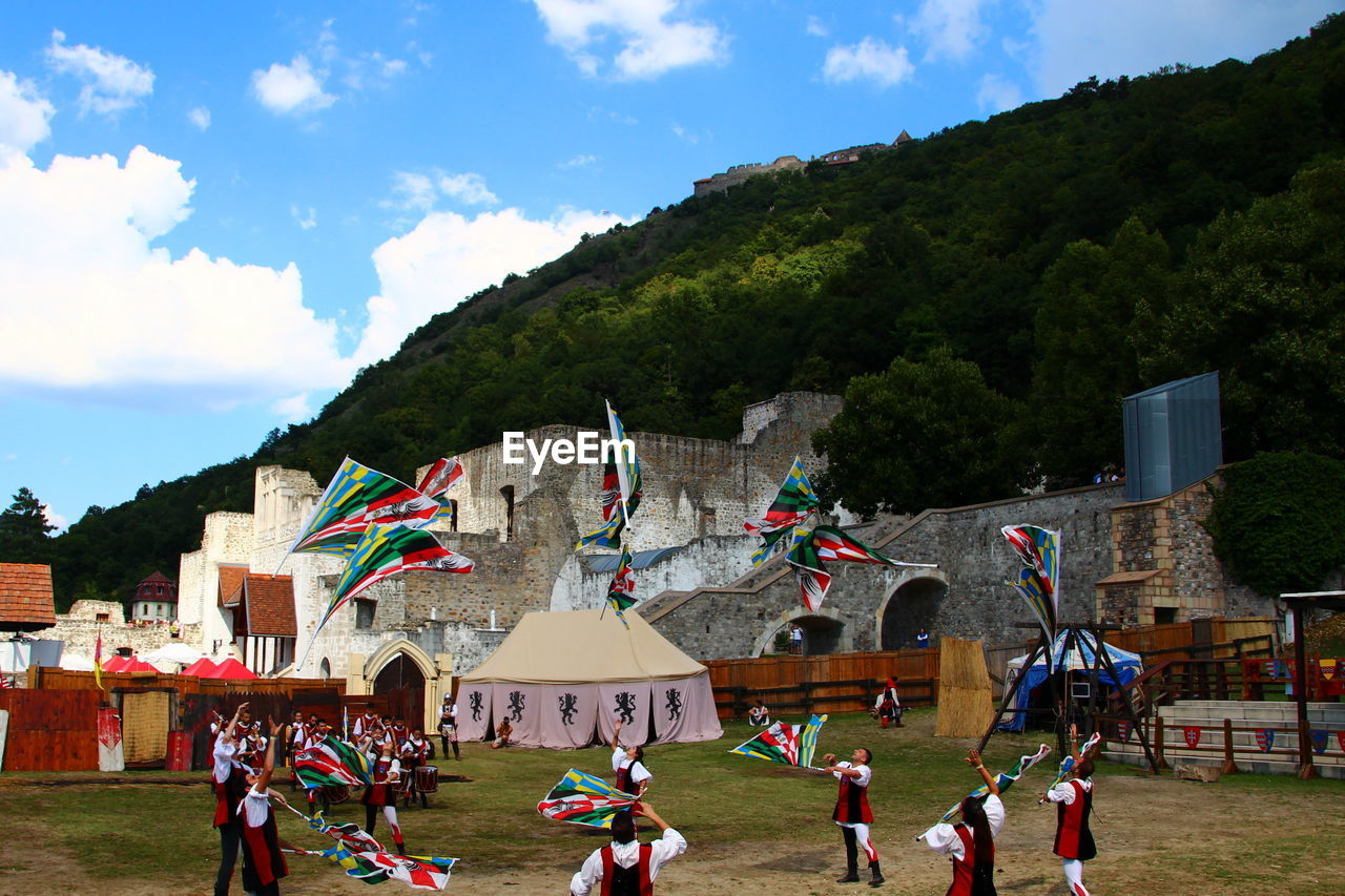 sky, group of people, tree, plant, cloud - sky, real people, crowd, nature, large group of people, mountain, men, day, architecture, built structure, leisure activity, outdoors, building exterior, building, sport
