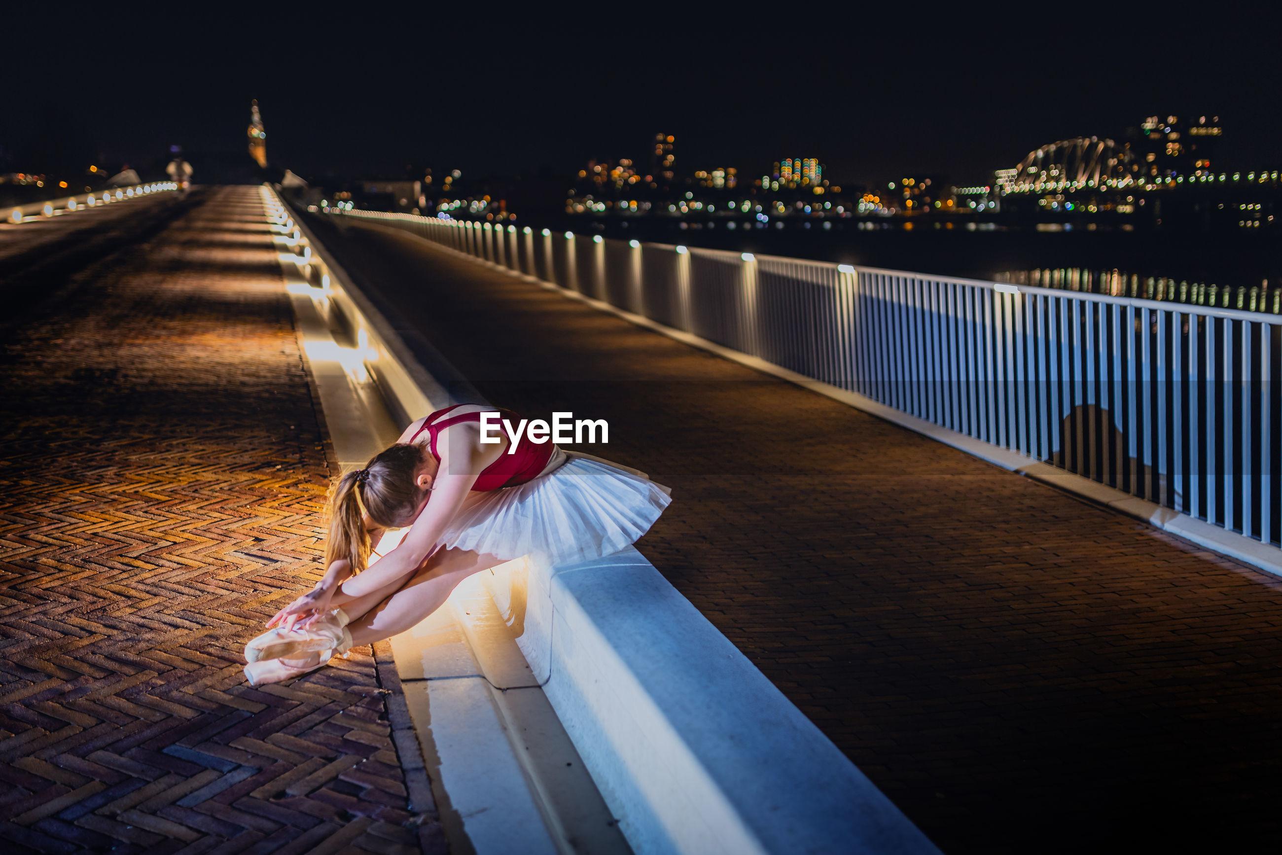Ballerina sitting by street at night