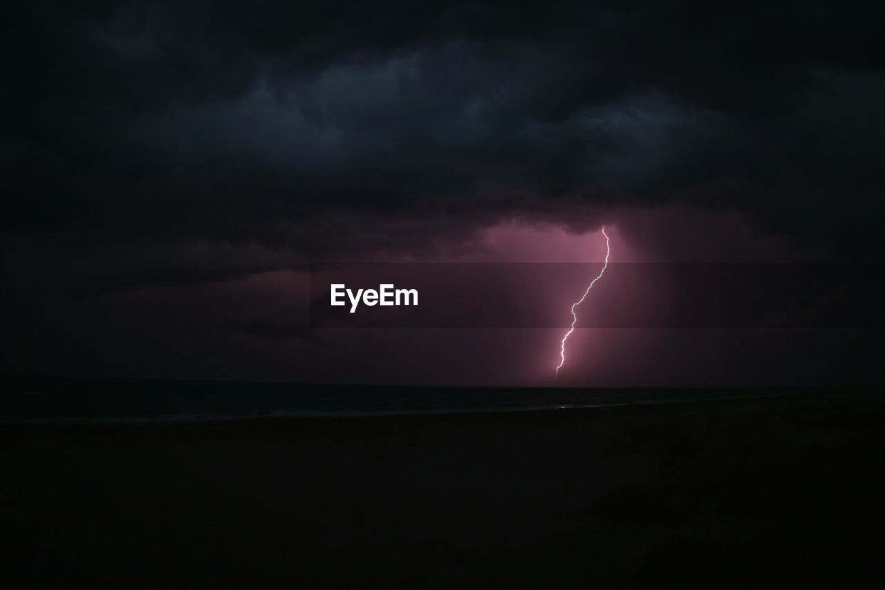 Scenic View Of Sea Against Lightning In Cloudy Sky