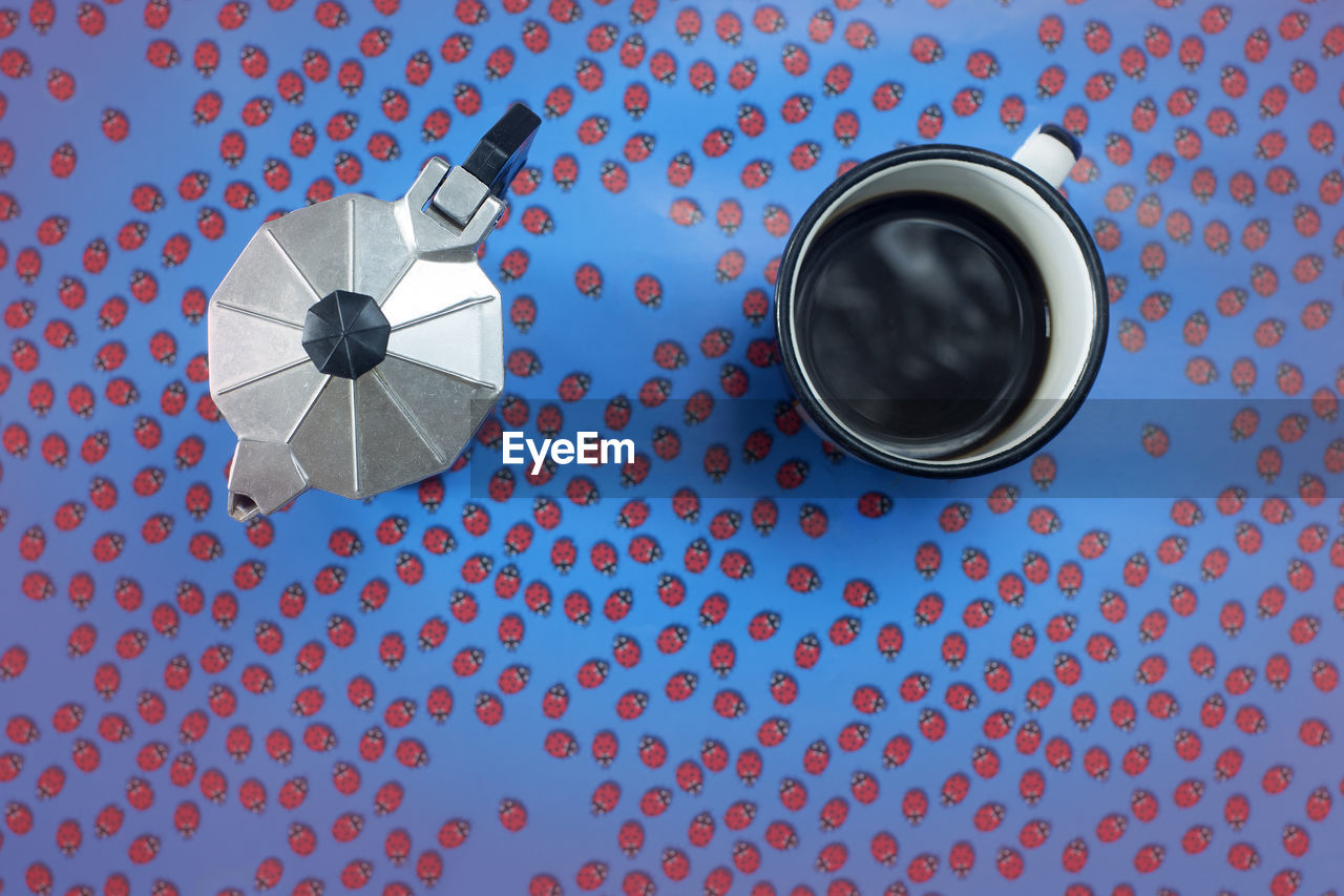 High Angle View Of Coffee Cup And Pot On Patterned Table