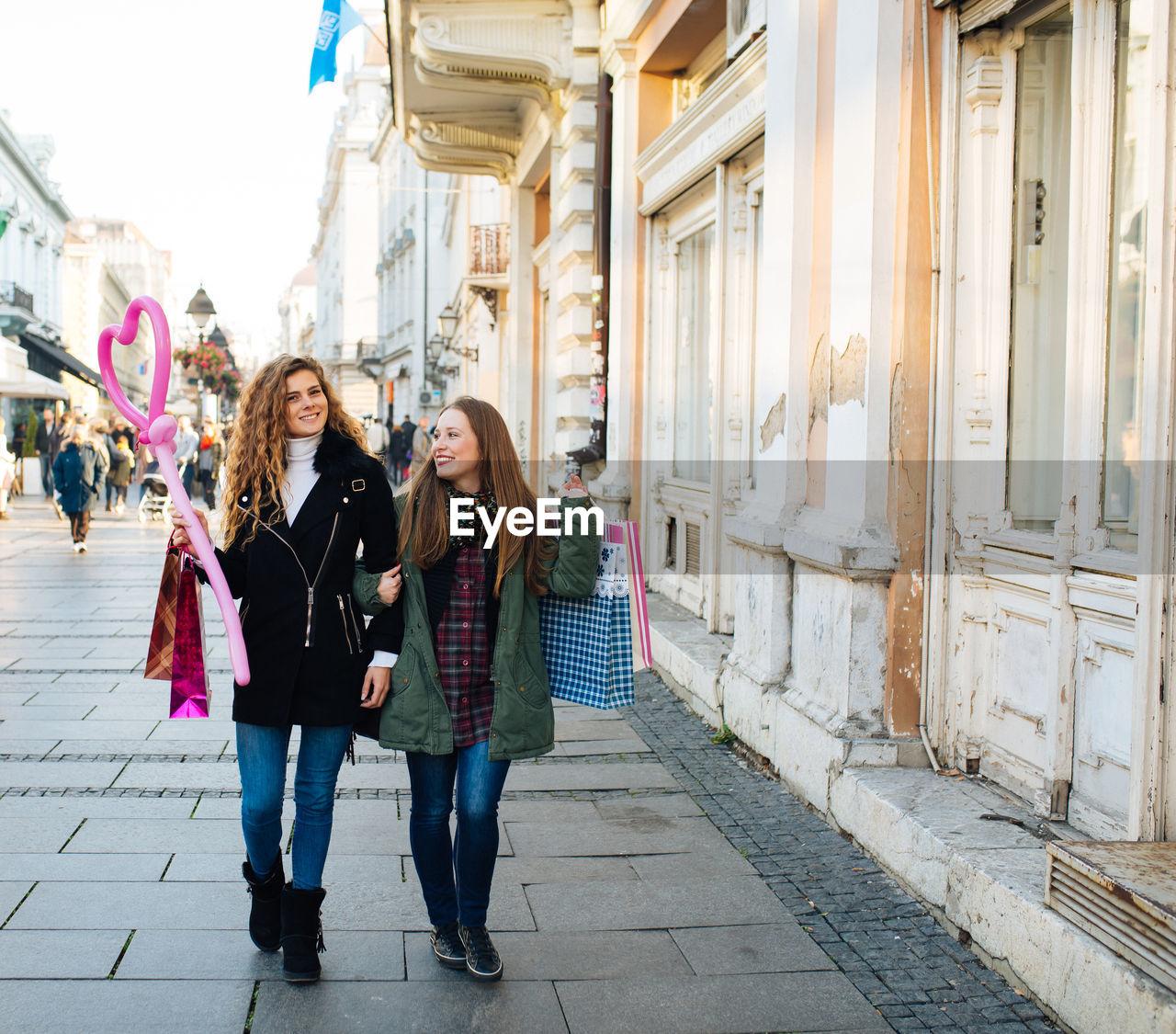 Full Length Of Friends Walking In City