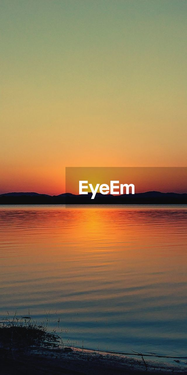 sunset, sky, water, beauty in nature, tranquility, scenics - nature, tranquil scene, silhouette, sea, orange color, no people, nature, idyllic, copy space, outdoors, non-urban scene, clear sky, horizon, romantic sky