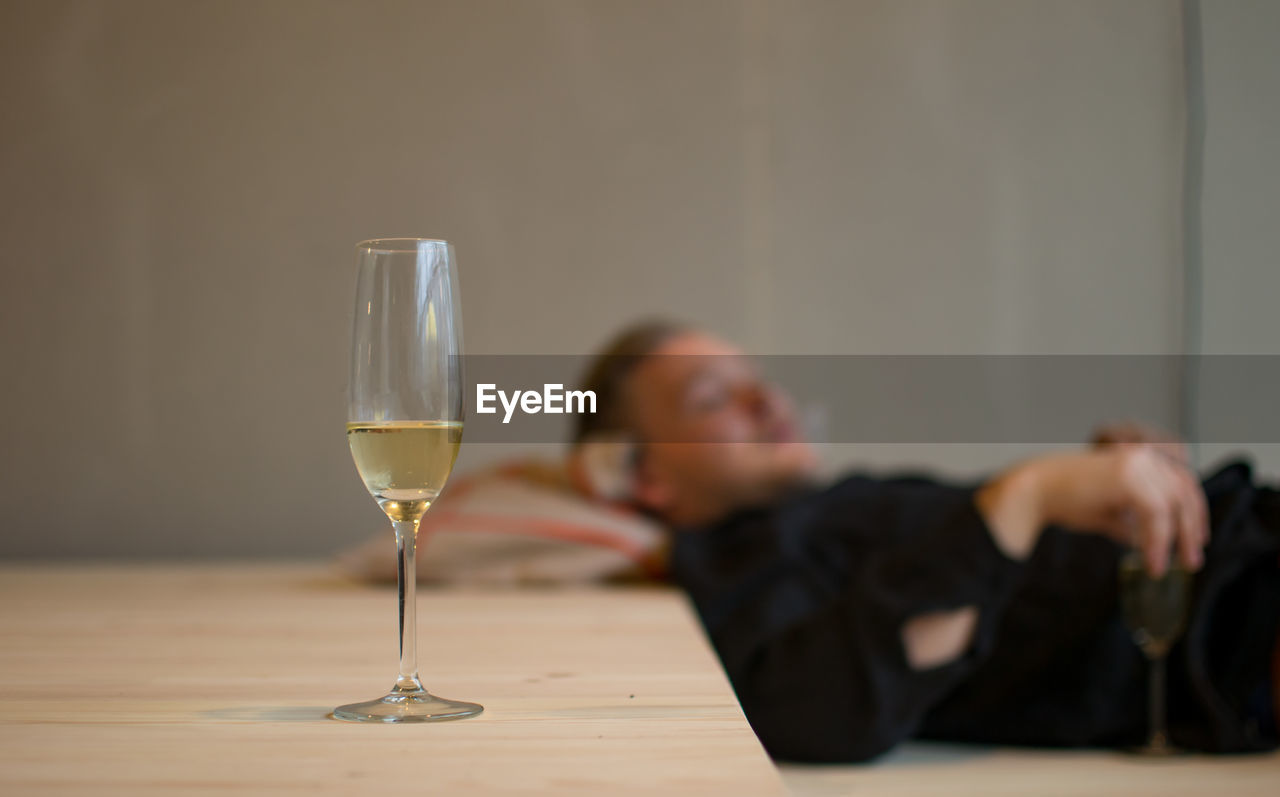 Champagne Flute On Table With Man Sleeping At Home