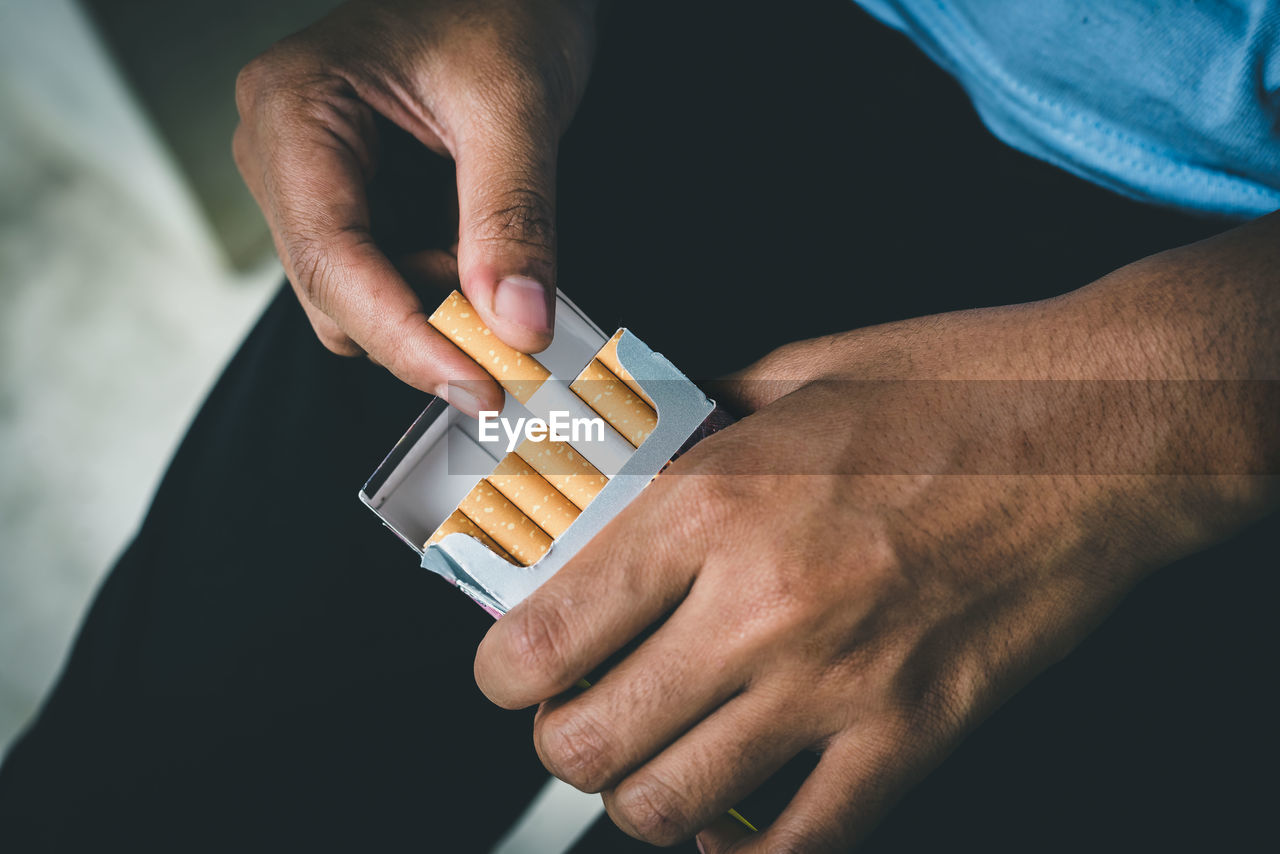 Close up man hand holding peel it off cigarette pack prepare smoking a cigarette. packing line up.