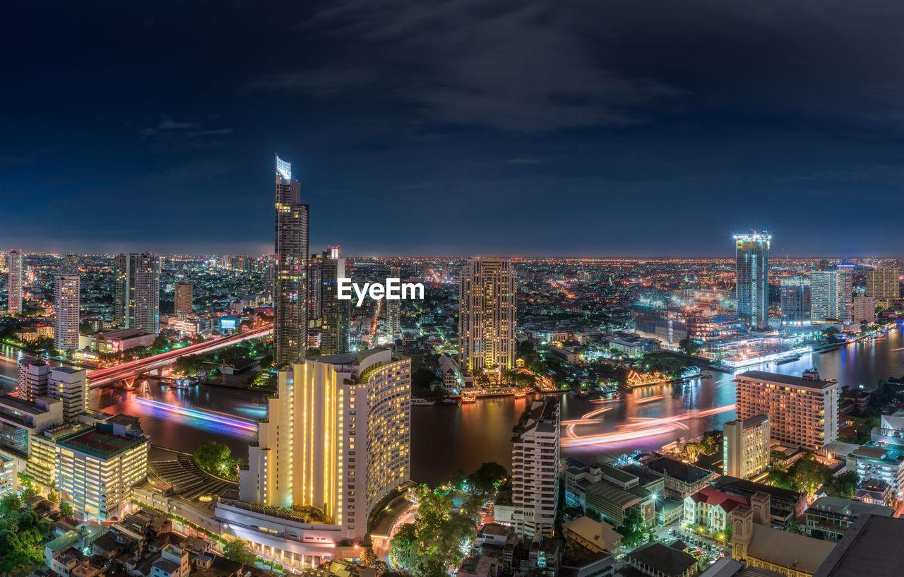 Illuminated Buildings Along Chao Phraya River In City Against Sky