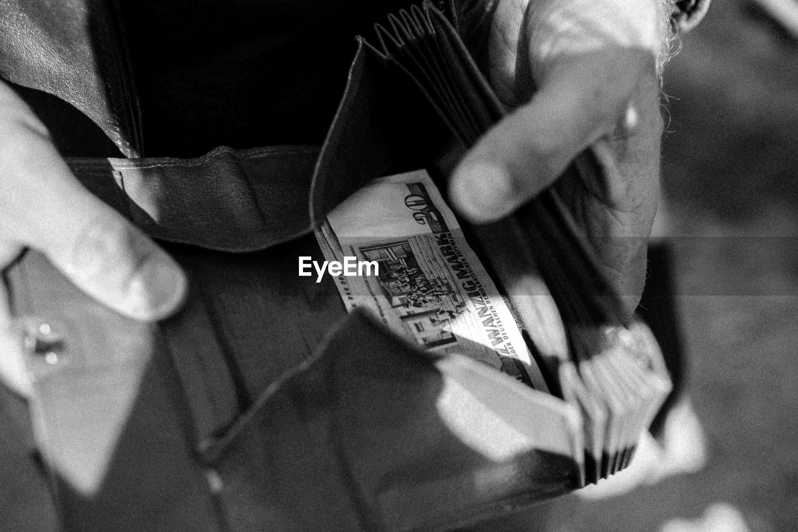 Cropped hands of man holding wallet with paper currency