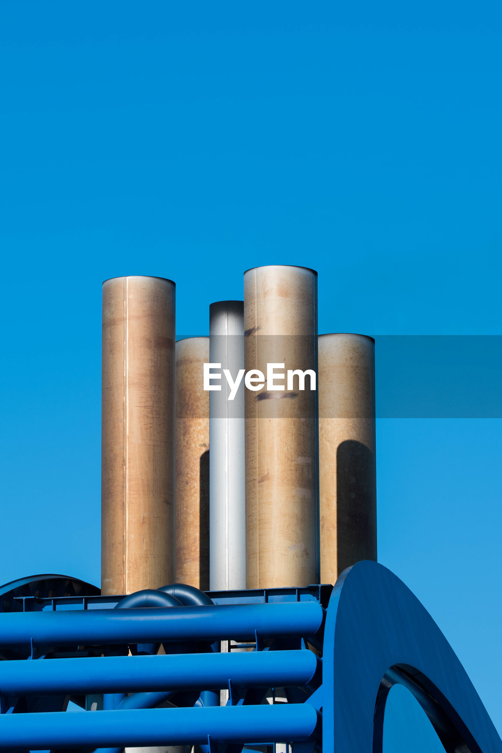 Low angle view of chimneys against clear blue sky