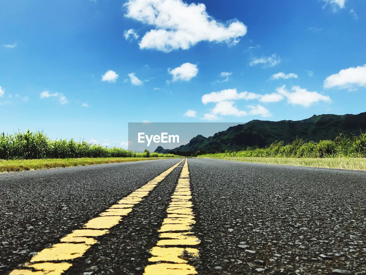 Surface level of empty road against blue sky