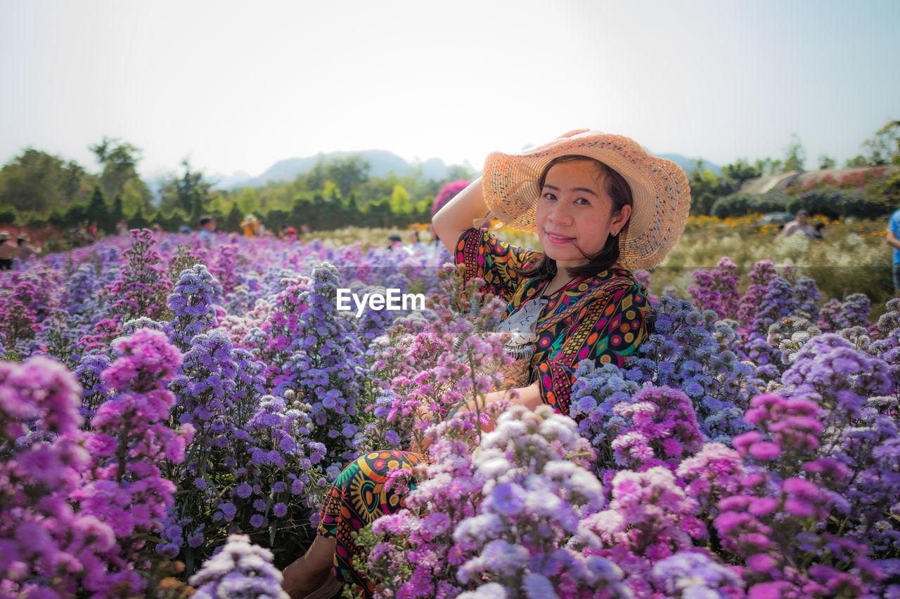 Portrait of woman with purple flowers on field