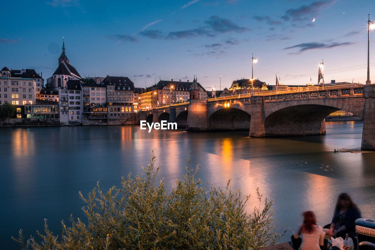 Friends sitting near illuminated bridge over river in city at dusk