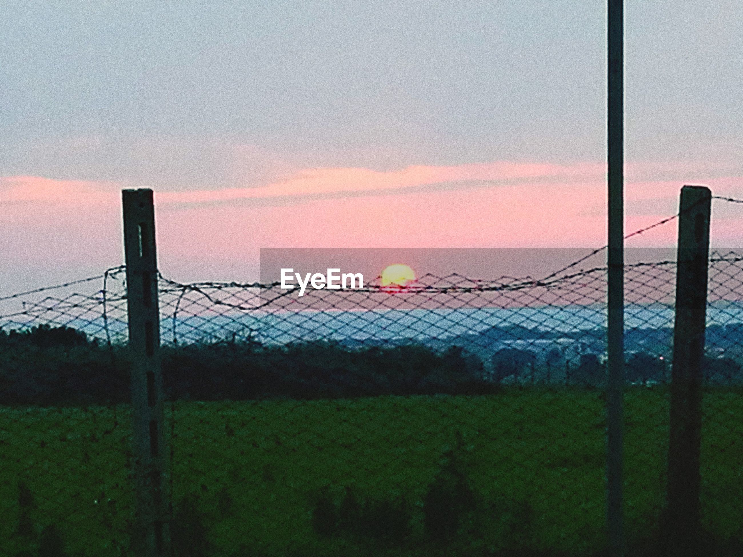 sky, sunset, safety, protection, chainlink fence, nature, no people, outdoors, field, grass, growth, beauty in nature, scenics, cloud - sky, playing field, sport, soccer field, beach volleyball, day