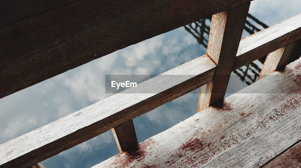 wood - material, railing, day, no people, water, nature, focus on foreground, outdoors, sea, seat, high angle view, bench, barrier, architecture, close-up, sky, sunlight, beauty in nature, fence, wood