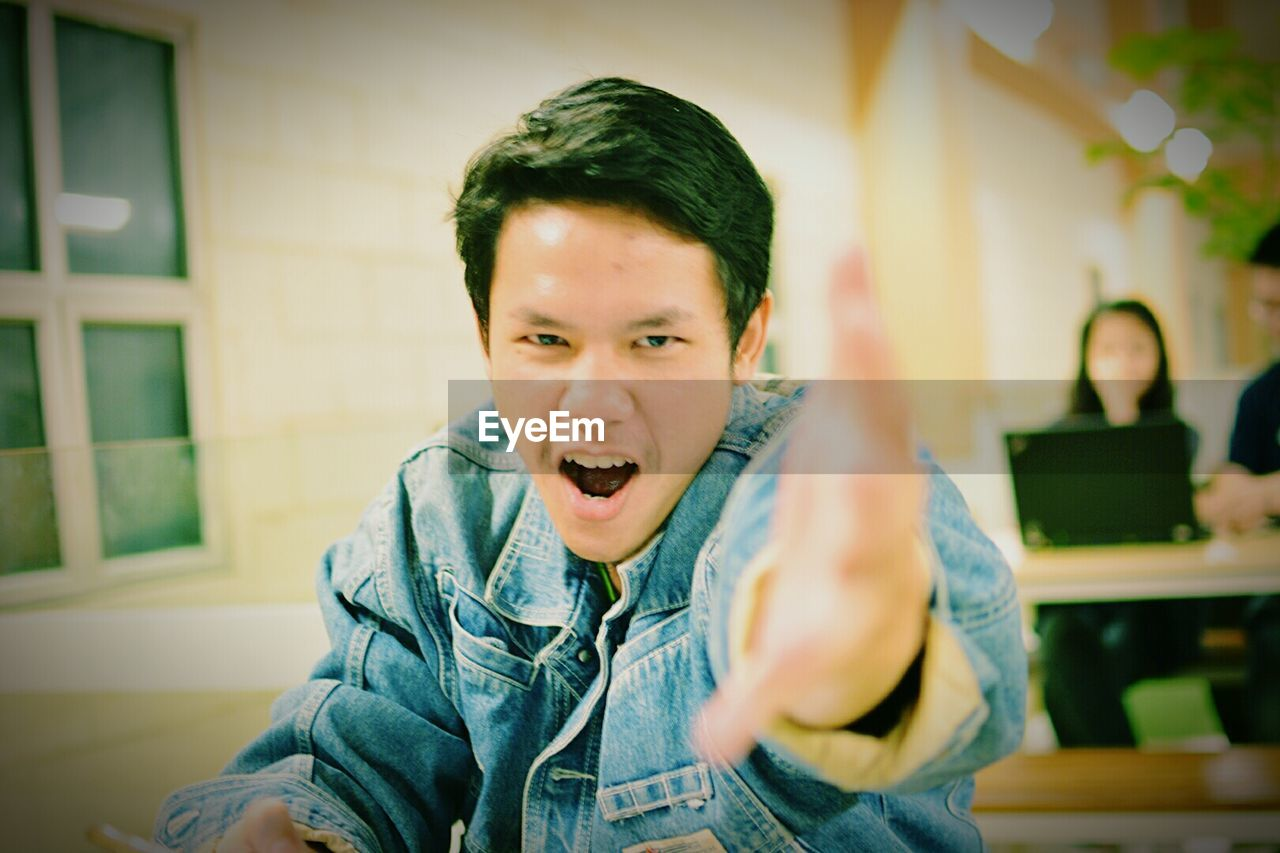 Portrait of university student gesturing in classroom