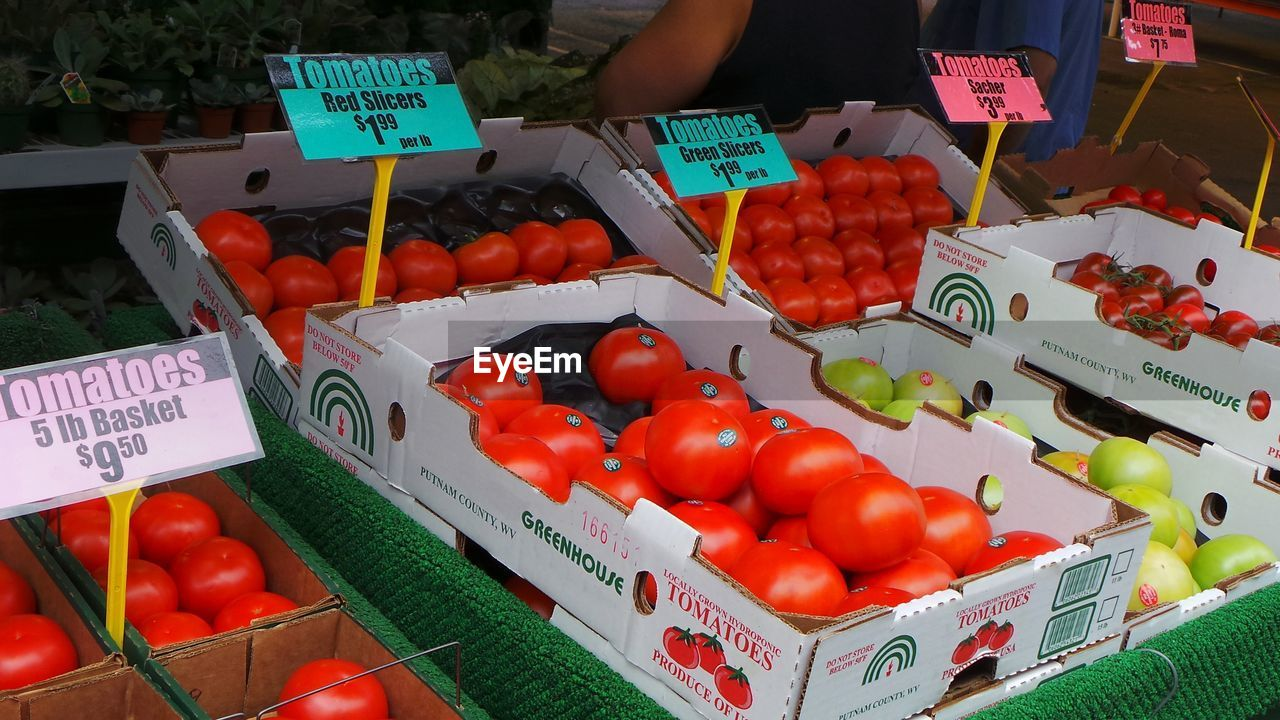 text, price tag, western script, communication, for sale, market stall, retail, market, vegetable, food, food and drink, number, high angle view, freshness, tomato, variation, outdoors, day, healthy eating, abundance, large group of objects, choice, no people