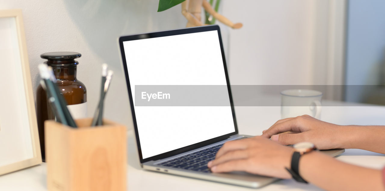 Person using laptop at desk in office